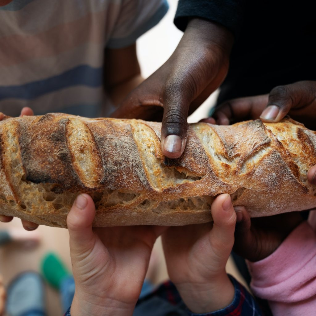 Black and white children holding loaf of bread